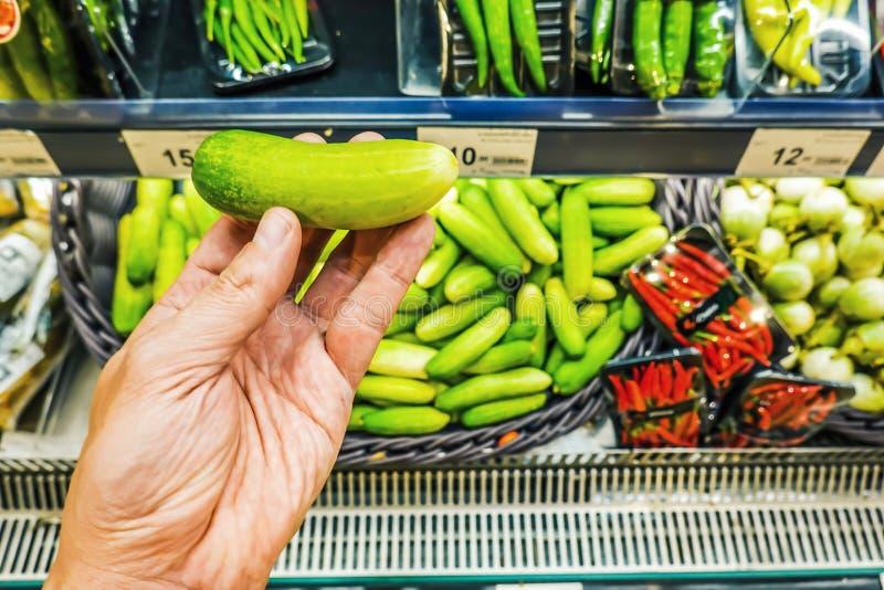 Die Hand des Mannes nimmt eine frische Gurke vom Nahrungsmittelregal Organische Produkte Gemüse und Früchte stockfoto