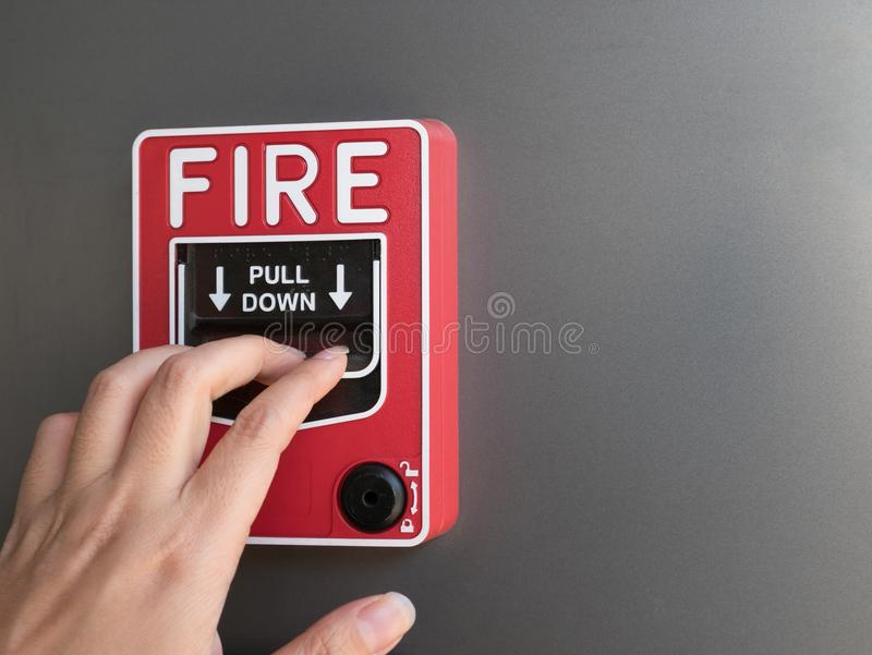 Die Hand des Mannes roten Feuermelder auf grauem Hintergrund ziehend lizenzfreie stockbilder