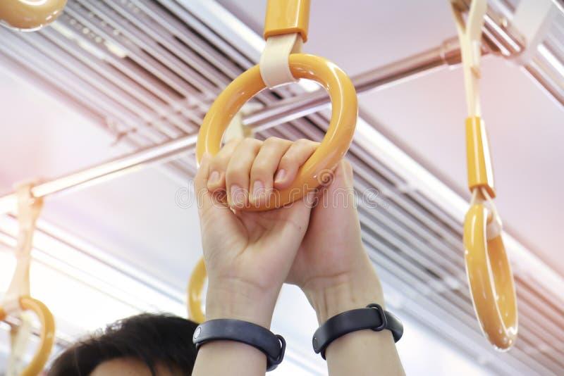 Die Hand des Mannes, welche im Zug die Hand einer Frau auf Kreisgriff während der Reise hält lizenzfreie stockbilder