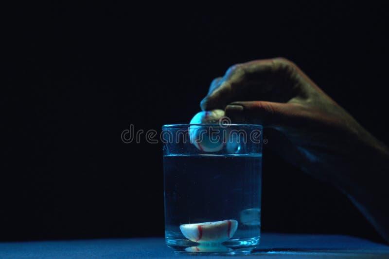 Die Hand des Zombies hält Augen über Glasbecher mit Flüssigkeit stockbilder