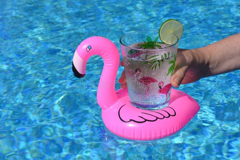 Die Hand, die ein Getränk in einem aufblasbaren rosa Flamingo hält, trinkt Halter im Swimmingpool stockbild