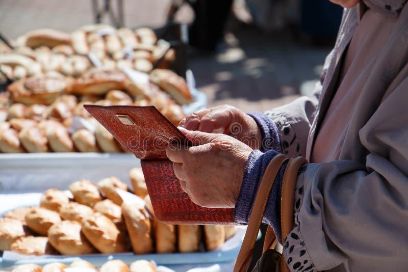 Die Hand einer älteren Frau, die Geld aus ihrem Geldbeutel heraus nimmt stockfotografie