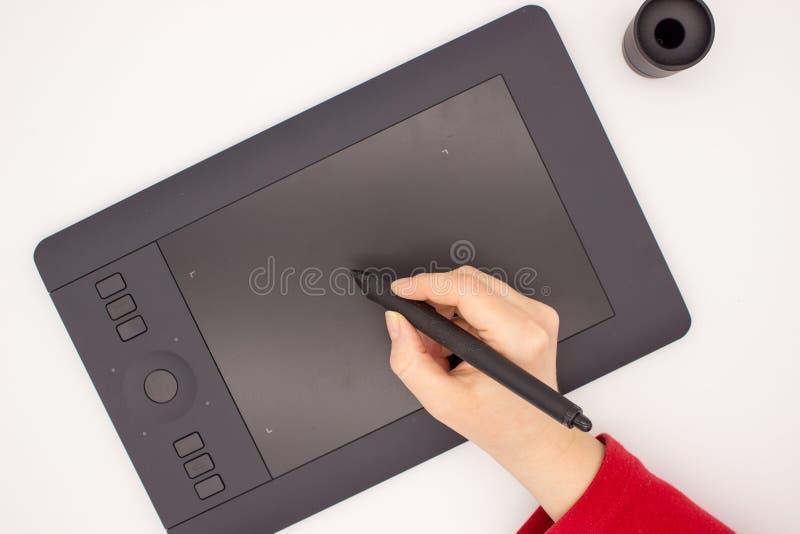 Die Hand einer Frau in einem roten Ärmel zeichnet einen Griffel auf einer Grafiktablette stockbild