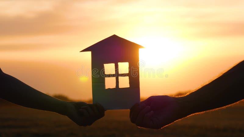 Die Hand einer Frau hält ein Papierhaus und führt es zur Hand eines Mannes Haus bei Sonnenuntergang stockfotos