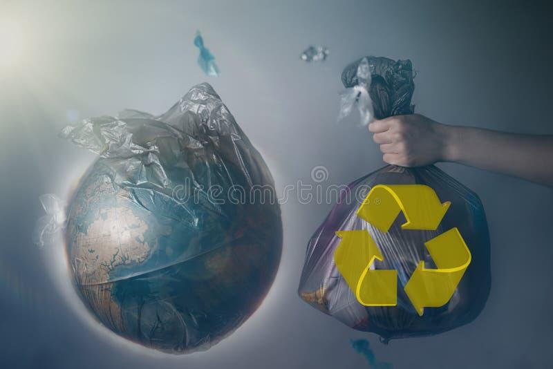 Die Hand einer Frau h?lt eine Abfalltasche nahe bei der Kugel von Planet Erde Konzept von ?kologie und von Umweltschutz Das recyc lizenzfreie stockfotografie