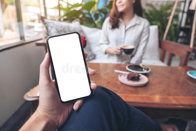 Die Hand eines Mannes, die schwarzen Handy mit leerem weißem Schirm mit der Frau sitzt im Café hält stockfotografie