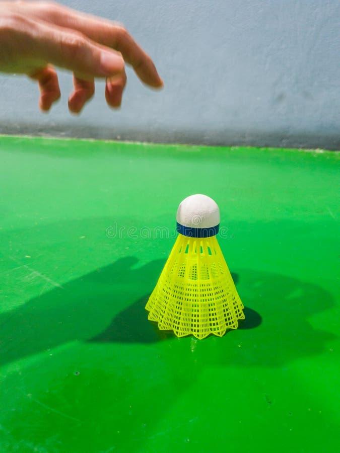 Die Hand, die grünen Plastikbadmintonfederball mit Federballplatzhintergrund auswählt stockfoto