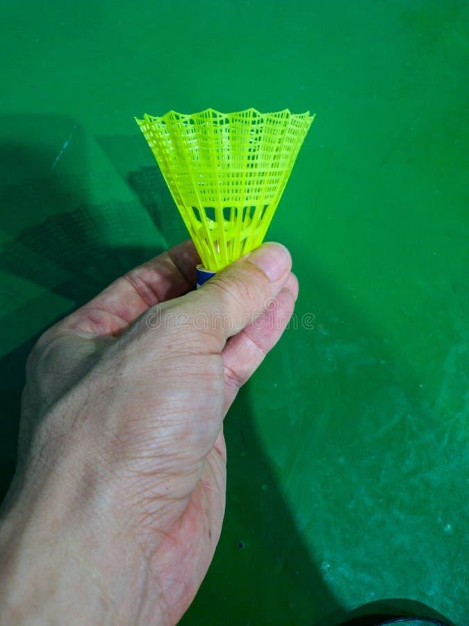 Die Hand, die grünen Plastikbadmintonfederball mit Federballplatzhintergrund hält stockbild