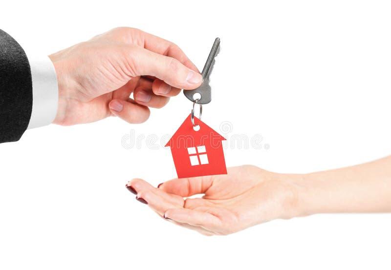 Die Hand hält die Schlüssel mit dem roten Haus keychain Kauf von Wohnungen Haus in den Händen Abschluss oben Getrennt auf einem W stockfotos