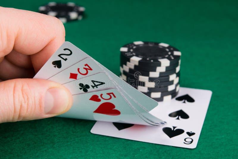 Die Hand hebt einen Satz Spielkarten an, um die Ausrichtung der Straße zu sehen, um die Rate zu erhöhen lizenzfreie stockfotografie