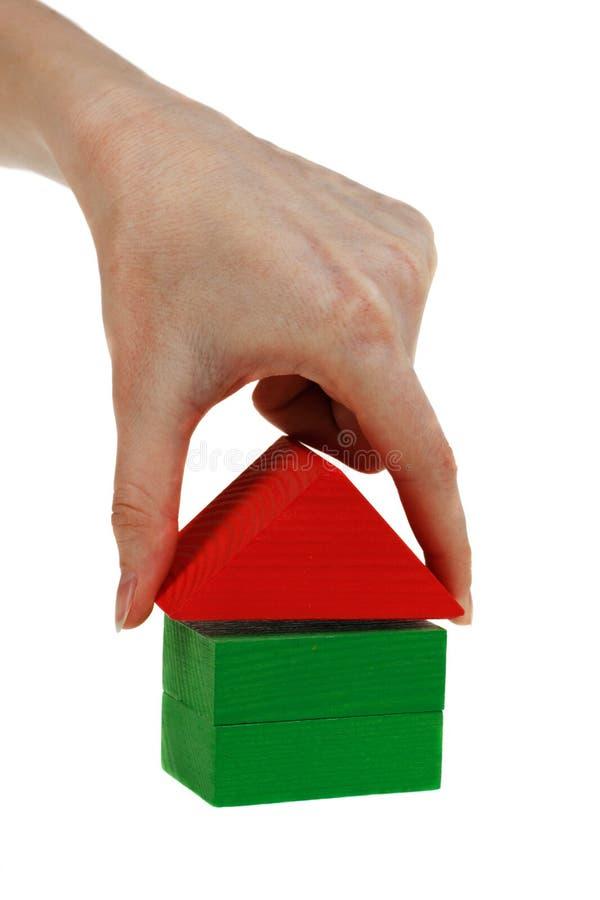 Die Hand legt ein Spielzeugdach auf hölzernen Würfeln fest lizenzfreie stockfotos