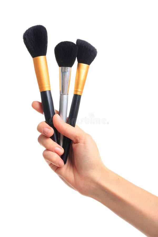 Die Hand, die Make-upbürsten auf Weiß hält, lokalisierte Hintergrund stockbild