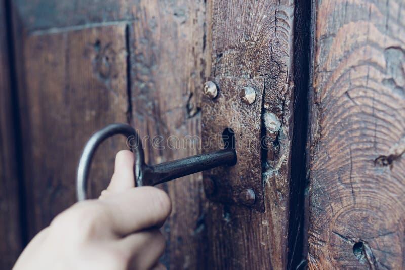 Die Hand, die Metallweinleseschlüssel zum Entriegeln altes geheimes hölzernes tun hält lizenzfreie stockfotografie