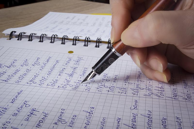 Die Hand schreibt in ein Notizbuch stockfotografie