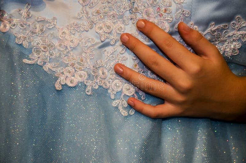 Die Hand und ein schönes, blaues Kleid einer Frau stockbild
