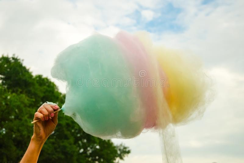 Die Hand von den Frauen, die farbige Zuckerwatte im backgrou halten lizenzfreie stockfotos