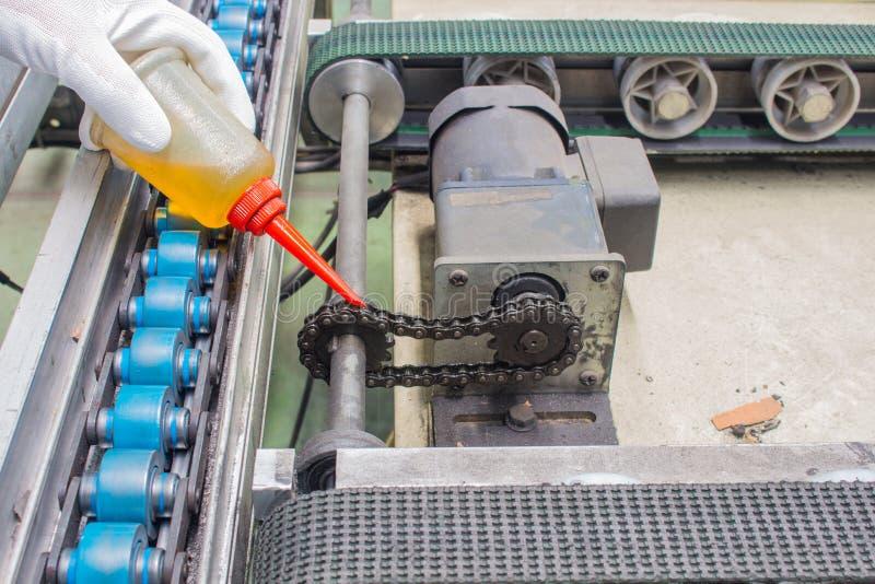Die Hand von Schmieröltropfen des Technikers zum Ketten-Antrieb für Wartung stockbild