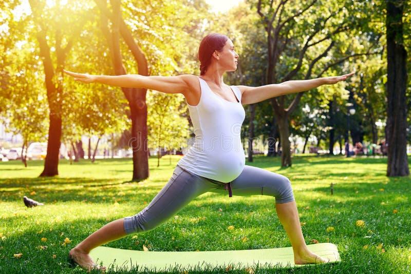 Die harmonische schwangere Frau, die im Yoga meditiert, werfen draußen auf stockfoto