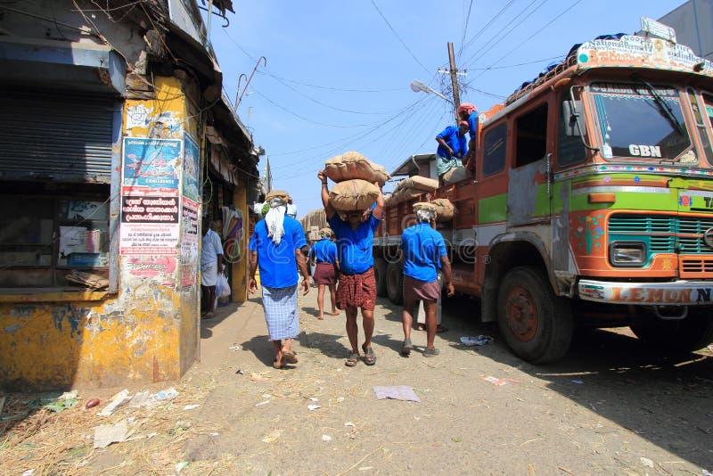 Die Hauptlastsarbeitskräfte, die Juteleinwand entladen, bauscht sich von einem LKW im Markt stockfotos