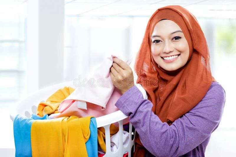 Die Hausfrau, die tragenden Wäschekorb der Hausarbeit voll von tut, kleiden lizenzfreie stockfotos