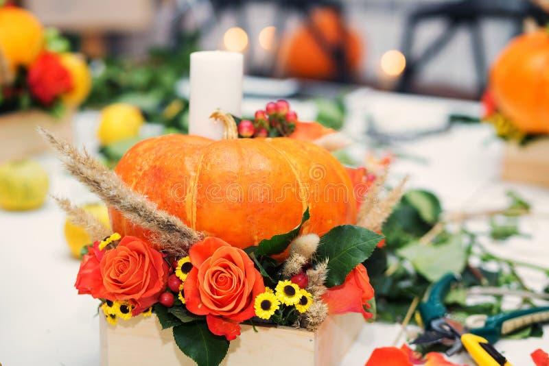 Die helle Herbstanordnung für Blumen und Beeren im Kürbis lizenzfreie stockfotografie