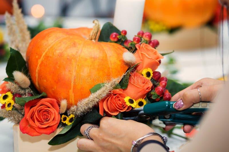 Die helle Herbstanordnung für Blumen und Beeren im Kürbis lizenzfreie stockbilder