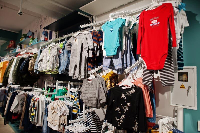 Die helle Kleidung der Kinder hängt an der Anzeige im BabyBekleidungsgeschäft Jungenabschnitt stockfotos