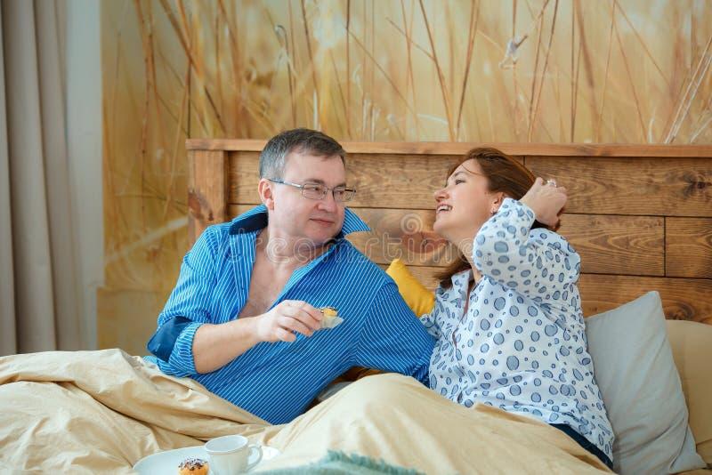 Die helle Teeschale mit einem heißen Getränk Ehemann holte seinen Frauteekaffee zum Bett stockfotografie