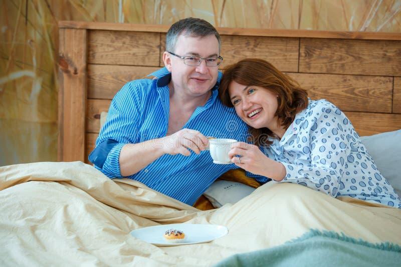 Die helle Teeschale mit einem heißen Getränk Ehemann holte seinen Frauteekaffee zum Bett stockbild