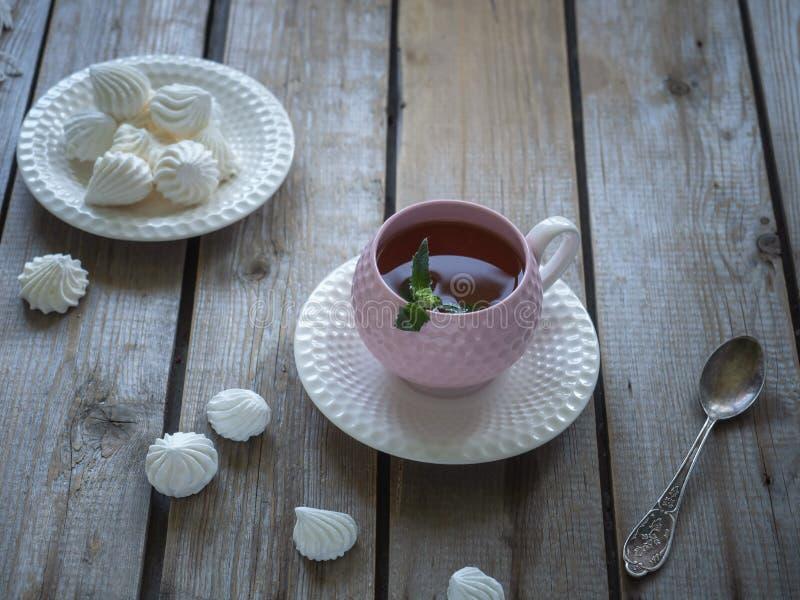 Die helle Teeschale mit einem hei?en Getr?nk Keramischer dekorativer Vase Meringeplätzchen, Zusammensetzung auf einem Holztisch stockfotografie