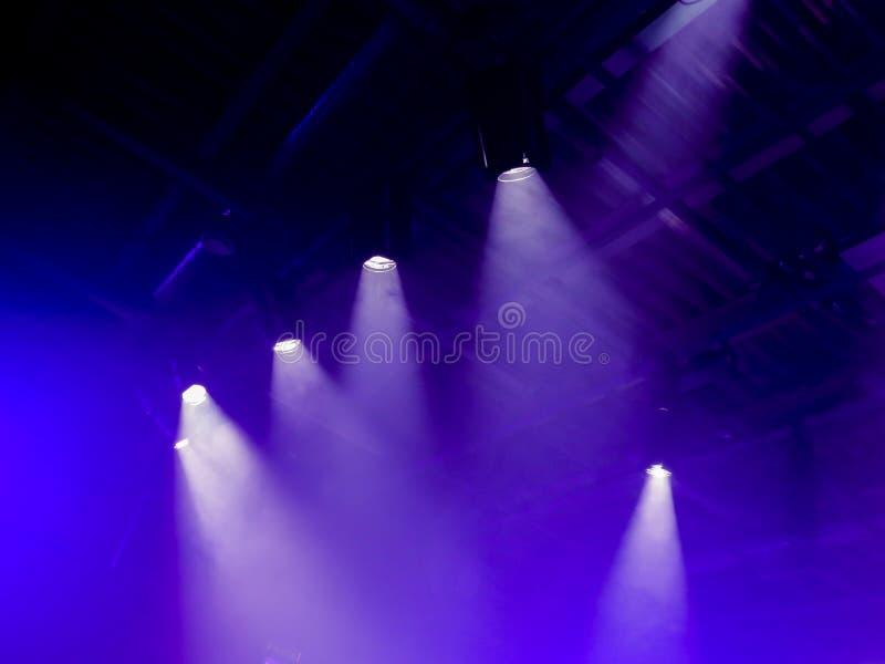 Die hellen Strahlen vom Scheinwerfer durch den Rauch Lichttechnische Ausrüstung auf der Decke lizenzfreie stockfotografie