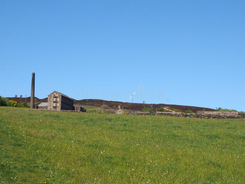 Die hellgrüne Graswiese, die herein auf einem Abhang mit dem alten Mühlkamin bedeckt werden und die Steinhaushäuser an der alten  lizenzfreie stockfotos