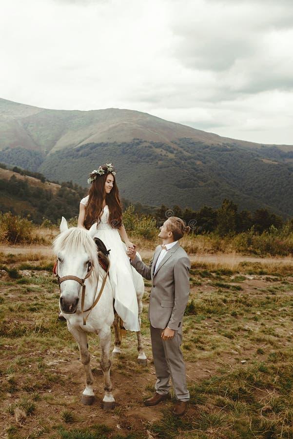 Die herrliche Braut, die einen Schimmel und einen stilvollen Bräutigam reitet, boho heiraten stockfoto