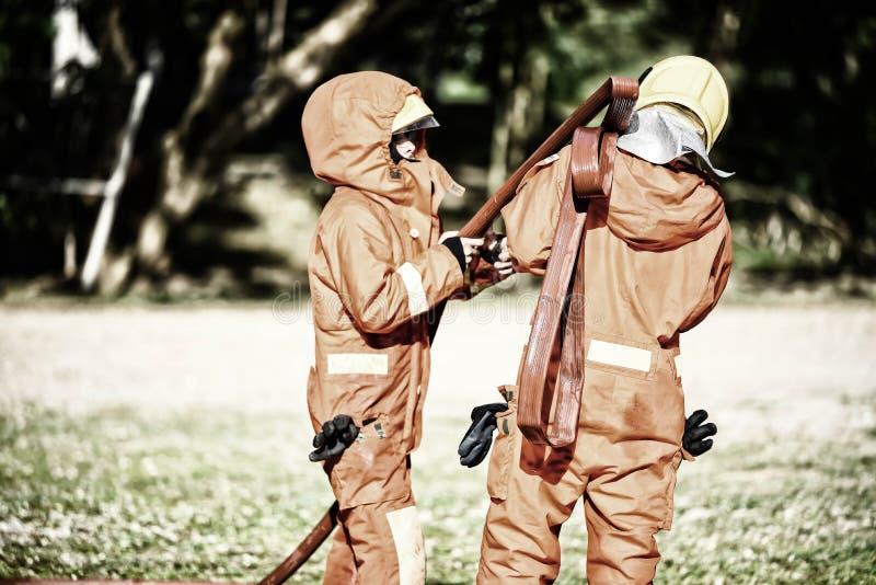 Die Hilfe mit zwei Feuerwehrmännern vereinbaren den Wasserschlauch, um das Feuer zu kämpfen Feuerwehrmann bereiten sich ankleiden stockfoto