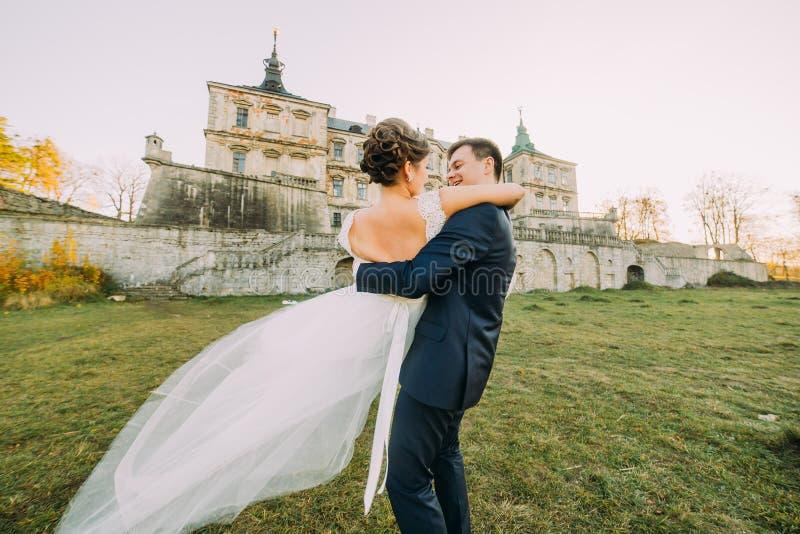 Die hintere Ansicht der Braut spinned durch den lächelnden Bräutigam Die Zusammensetzung des gotischen Schlosses lizenzfreie stockfotos