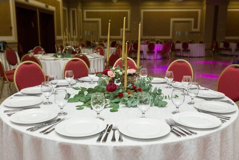 Die Hochzeitstafeleinstellung wird mit frischen Blumen in einer Messingschüssel und goldenen Kerzen in den Messingkerzenleuchtern lizenzfreie stockfotos