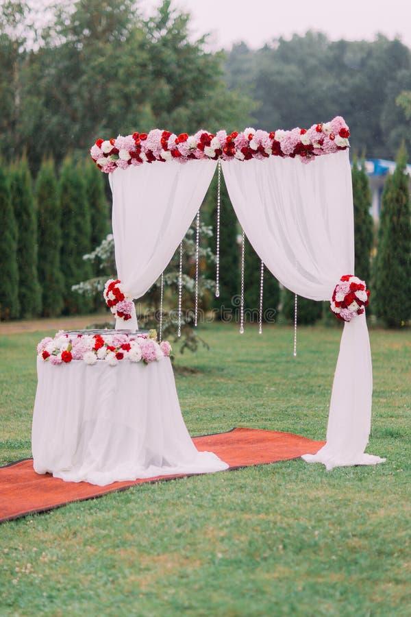 Die Hochzeitszusammensetzung des Hochzeitsbogens und -tabelle verziert mit bunten Blumen und hängenden Perlen lizenzfreie stockfotografie