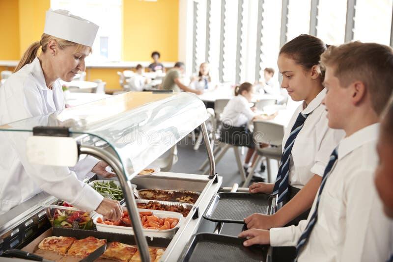 Die hohen Schüler, die einheitliches Wesen tragen, dienten Nahrung in der Kantine lizenzfreie stockbilder