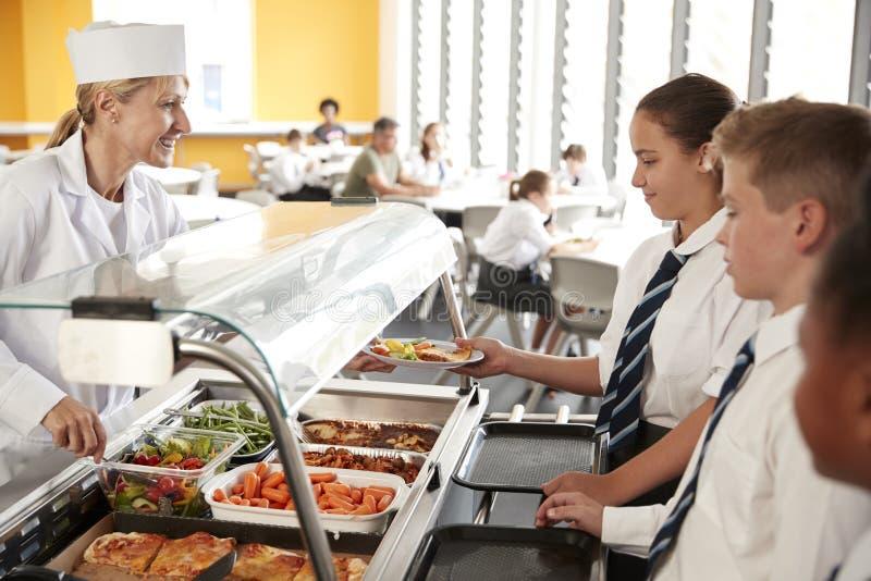 Die hohen Schüler, die einheitliches Wesen tragen, dienten Nahrung in der Kantine stockbild