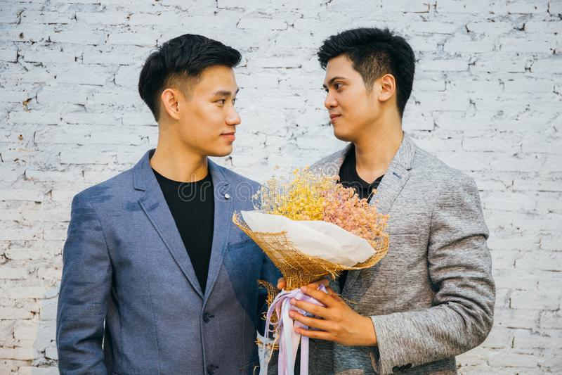 Die homosexuellen Paare, die einen Blumenstrauß von Blumen halten, bereiten vor, um zu geben seinem Partner für spezielle Gelegen stockfotografie
