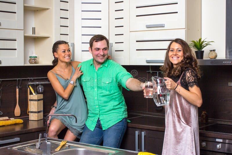 Die Hosteß bietet Gästen ein Glas Wasser in der Küche an stockfotografie