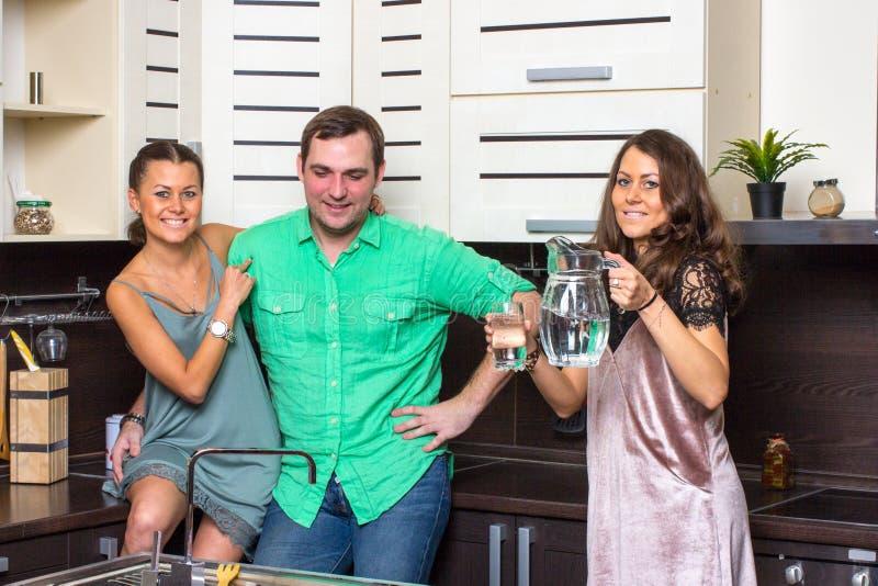 Die Hosteß bietet Gästen ein Glas Wasser in der Küche an lizenzfreie stockbilder