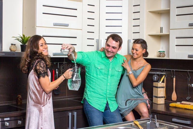Die Hosteß bietet Gästen ein Glas Wasser in der Küche an stockfoto