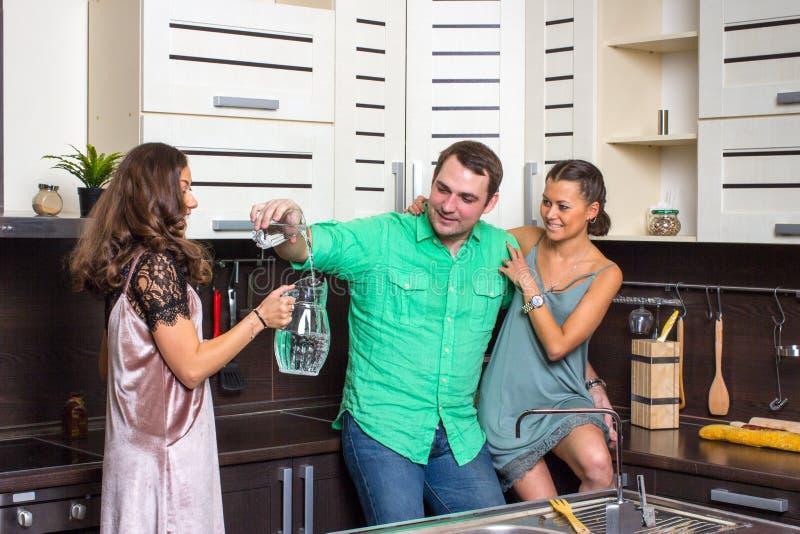 Die Hosteß bietet Gästen ein Glas Wasser in der Küche an lizenzfreie stockfotos