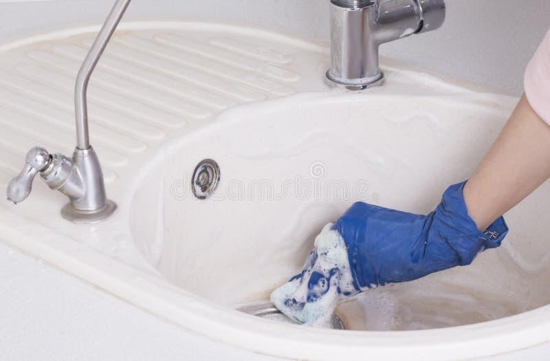 Die Hostess fing an, die Küche zu reinigen, die Waschbecken wasche stockbild