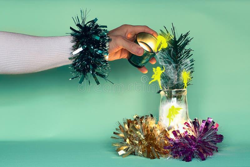 Die improvisierte Hand des Zauberers am Vorabend des neuen Jahres verströmt Märchenlicht von einem Glas zum anderen Haare Kreatur lizenzfreie stockbilder