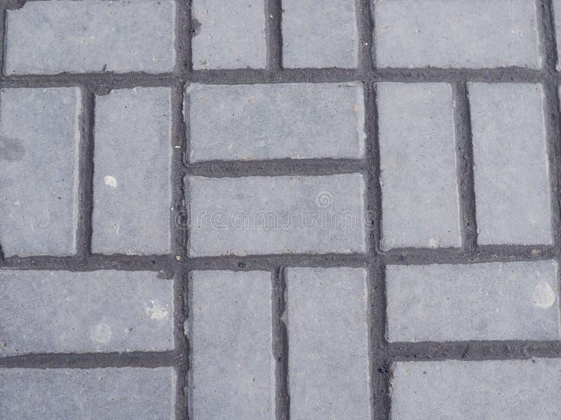 Die Ineinander greifenpflasterung mit grauem und weißem Baugewerbe konkrete Produkte der Betonblöcke pflasterte Boden lizenzfreie stockfotos