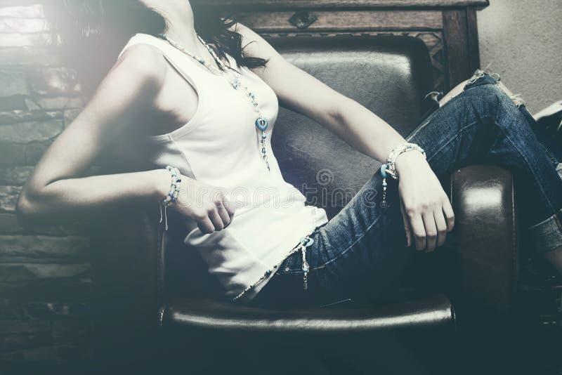 Die Innen Frau sitzen in tragenden Blue Jeans des Lehnsessels und weiße Behälterhemdarmbänder und -halskette lizenzfreies stockbild