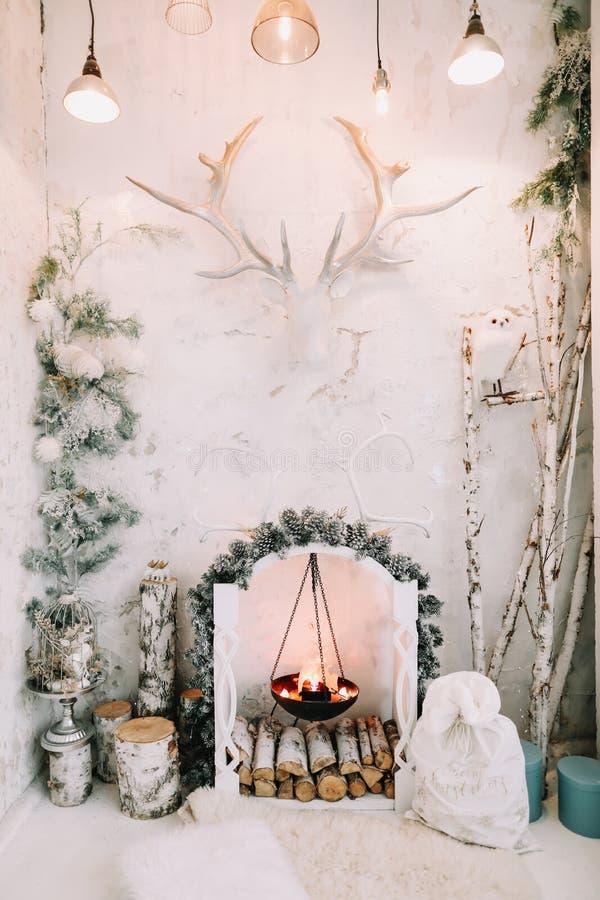 Die Inneneinrichtung ist klassisch und zu Weihnachten dekoriert Künstlicher Kamin Stilminimalistisch eingerichteter, weißer Wohnr stockbild