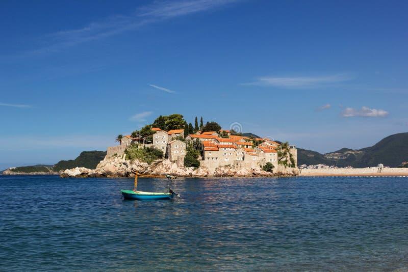 Die Insel von Sveti Stefan Boot auf dem Vordergrund lizenzfreie stockfotos